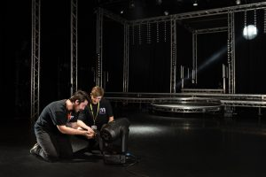 Two technicians with a theatrical light