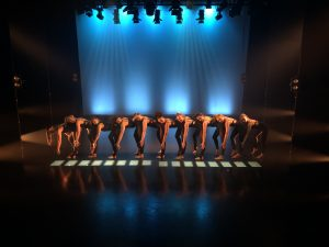 Miskin dancers in a line on stage