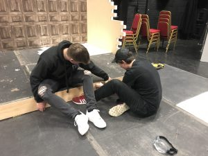 Two technicians working on the set for London Road