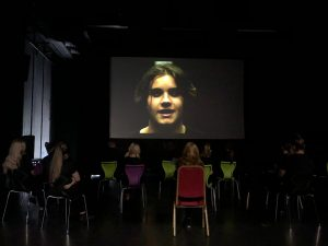 Actor on screen in studio theatre