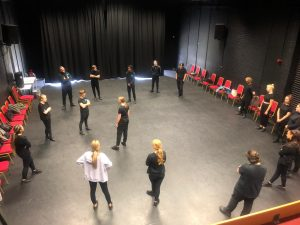 Group of actors standing in studio theatre