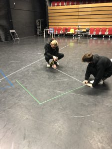 theatre technicians doing a floor mark up